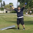 ASYC VP, Paul Cluck ,raises his arms in victory while doin a bean bag toss