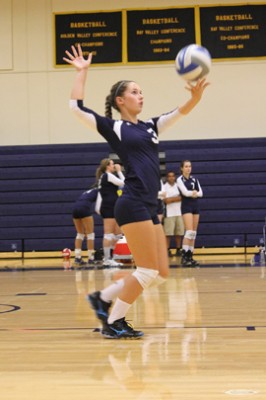 Allison Foster as she throws up a serve against Southwestern Oregon Community College | Photo by Alexis Pack