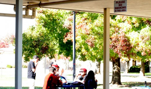 Yuba College students having a smoke break right outside the campus center nearby a sign that prohibits smoking in the area | Photo by Capa Lo