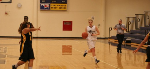 Kylie Nore attemps a drive for the basket as defenders watch her movement   Photo by Bob Barton