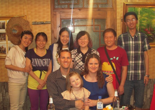 Professor Smith and his family seated at a dinner table; among them, students pose for the camera.