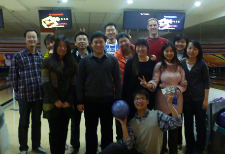 Professor Smith standing among his students in a bowling alley.