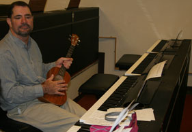 Sociology professor Mark Flacks holds a ukulele. A profound expression is upon his face.
