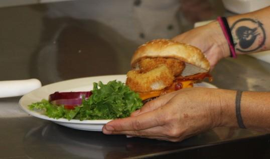 A student placing a western bacon cheeseburger.