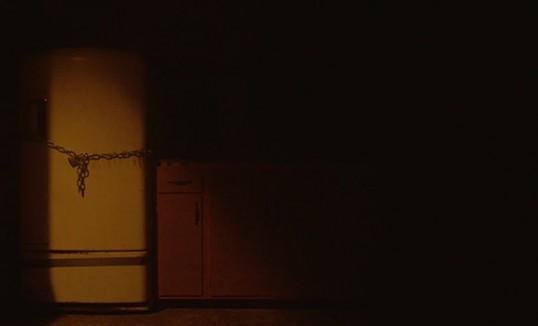 A locked fridge sits in darkness