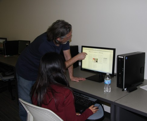 Mass Communications 20 adviser Greg Kemble and student Regina Hernandez work on the newspaper.