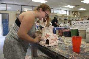 Yuba College student Haley Hurst paints her fish decor ceramics project. (Photo taken by Regina Hernandez)
