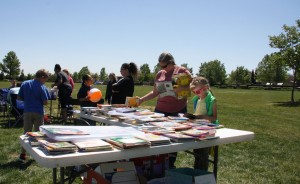 "Parents and children browse a variety of books donated by The Psychology Club at the ""Planting A Seed For Children's Growth"" event at the POW/MIA Edgewater park."