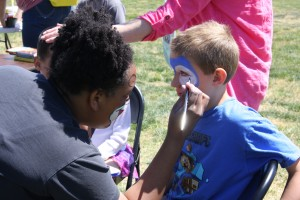 "Activities Coordinator Kapri Karcher face paints Sonic the Hedgehog on a child for the ""Planting A Seed For Children's Growth"" event at POW/MIA Edgewater Park."