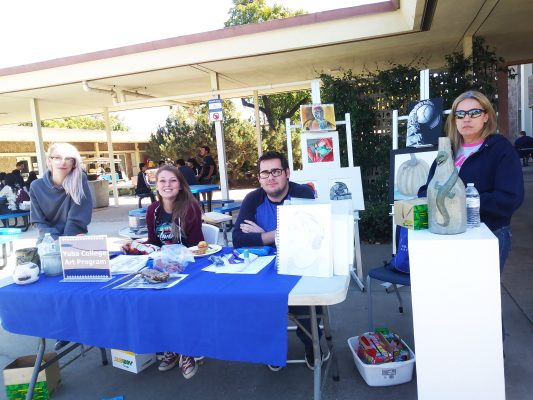 Yuba college art students sitting at booth