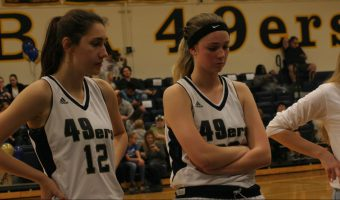 Jessica Taylor, Jenna Wilson number 12, and Mollie Townzen (right) listen in on the huddle